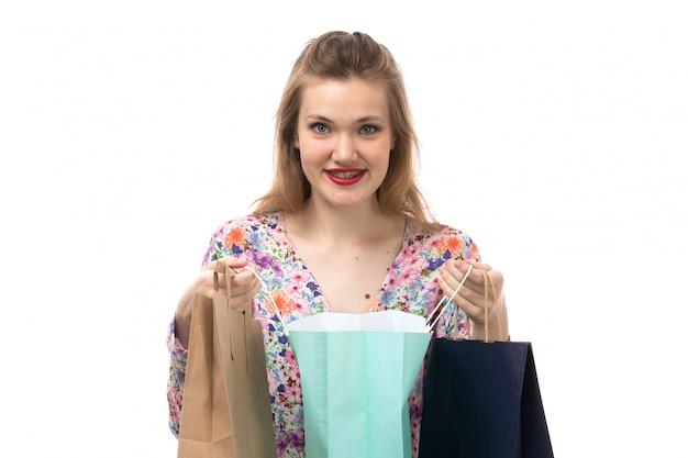 花の正面図の若い美しい女性のデザインのシャツと笑顔のショッピングパッケージを保持している黒いズボン