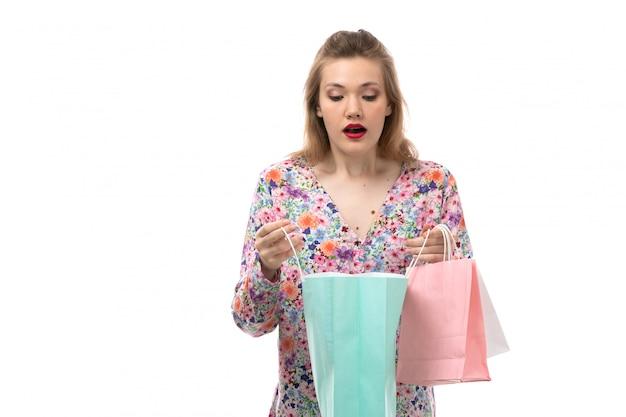 花の正面の若い美しい女性のデザインのシャツとショッピングパッケージを保持している黒いズボンはチェックを驚かせた