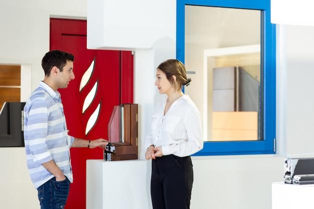 昼間の建物の仕事の活動中に何かを議論する若い男と一緒に白いシャツ黒ズボンの正面の若い美しい女性