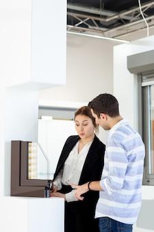 Вид спереди молодая красивая женщина в белой рубашке темной куртке черные брюки вместе с молодым человеком, что-то обсуждали во время дневного строительства работу