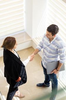 Вид спереди молодой бизнесмен в полосатой рубашке вместе с молодой бизнес-леди, обсуждая вопросы работы, говорить во время дневной работы
