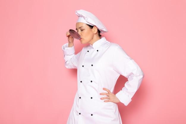 白いクックスーツホワイトキャップポーズ大きな銀のスプーンのおいしい食事を保持している正面の若い女性クック