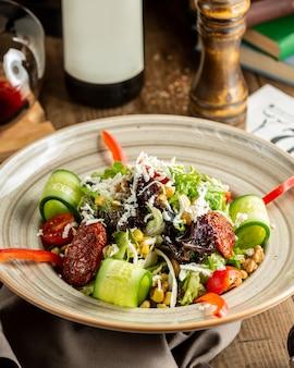 キュウリ、レタス、乾燥トマト、トウモロコシ、クルミの新鮮野菜のサラダ