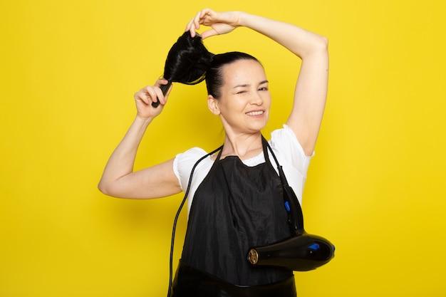 Вид спереди молодая женщина-парикмахер в белой футболке, черной накидке, расчесывающей волосы, позирующей