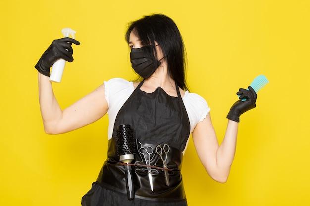 Вид спереди молодой женщины-парикмахера в белой футболке, черной накидке, держащей спрей, и расчески в черной стерильной маске, черные перчатки