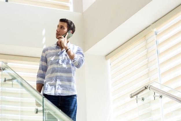 ストライプのシャツで話していると昼間の仕事活動の構築中に電話で仕事の問題を議論する正面の若いハンサムな男