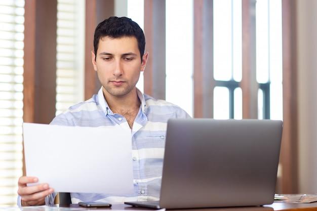 Вид спереди молодой красавец в полосатой рубашке, работающих в конференц-зале, используя свой серебряный ноутбук, просматривая документы во время дневной работы