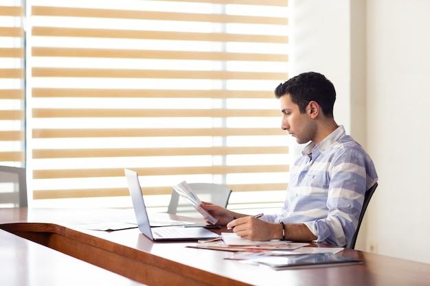 昼間の作業活動の構築中にドキュメントを探している彼の銀のラップトップを使用して会議ホール内で作業するストライプのシャツで正面の若いハンサムな男