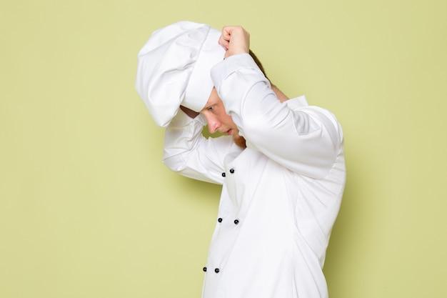 白いヘッドキャップを身に着けている白いコックスーツで正面の若い男性コック