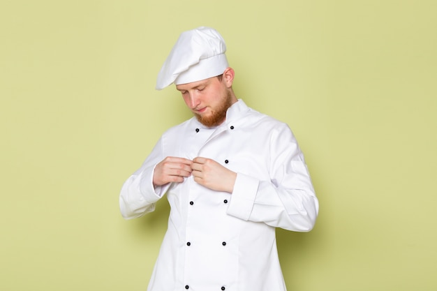 彼の布を修正する白いコックスーツホワイトヘッドキャップの正面図若い男性コック