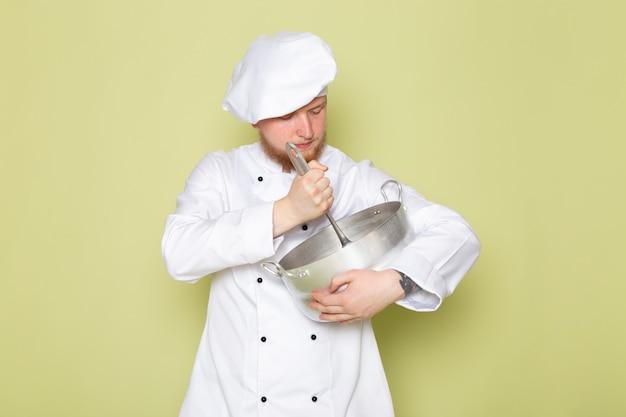 Вид спереди молодой самец повара в белом костюме повара белая шапка держит серебряную кастрюлю