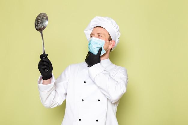 Вид спереди молодой самец повара в белом костюме повара белая шапка в черных перчатках синяя защитная маска с большой металлической ложкой в раздумьях