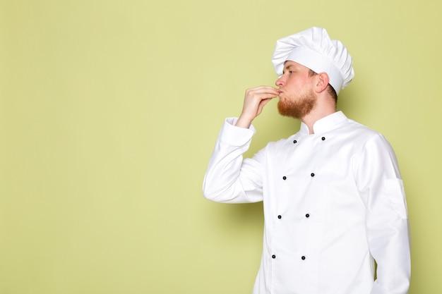 白いコックスーツホワイトヘッドキャップの正面の若い男性料理人