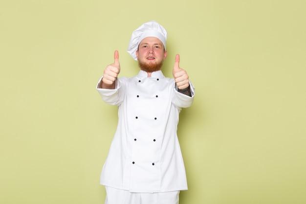 素晴らしい兆しを見せている白いコックスーツホワイトヘッドキャップの正面の若い男性コック