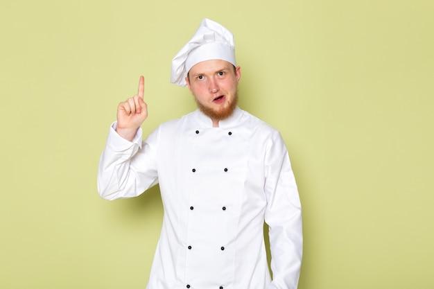 正面図の若い男性クックホワイトクックスーツ上げられた指で白いヘッドキャップ