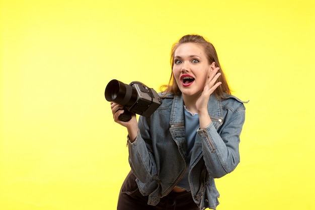 写真のカメラを保持している驚きの表情をポーズ青いシャツ黒のズボンとジーンズのコートでポーズをとって正面若い現代女性