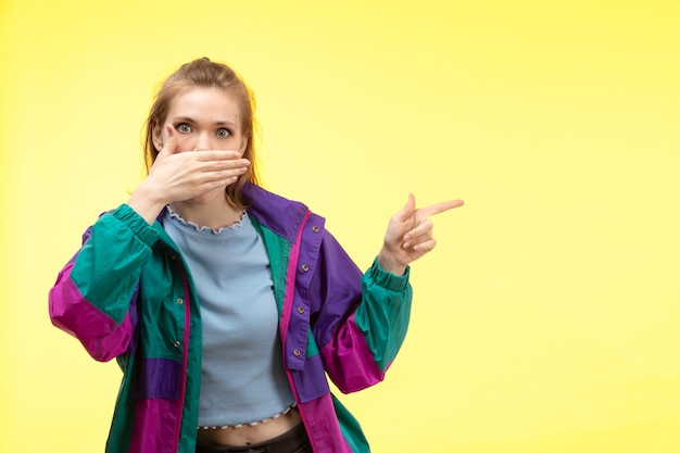 正面から見た青いシャツの黒いズボンのカラフルなジャケットの若い女性はショックを受けて指差しポーズを笑って