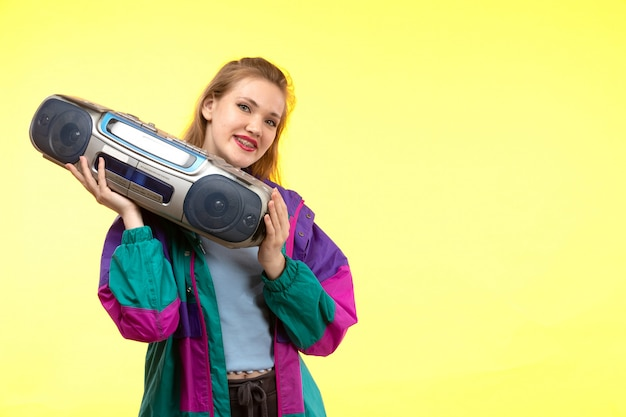 青いシャツ黒ズボンカラフルなジャケットのポーズを保持しているテープレコーダーを笑顔で正面の若い現代女性