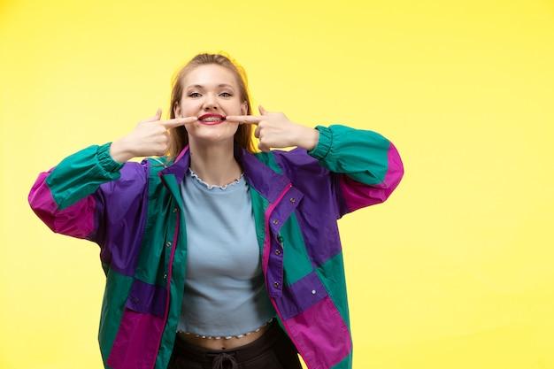 青いシャツの黒いズボンのカラフルなジャケットのポーズを笑顔で正面の若い現代女性