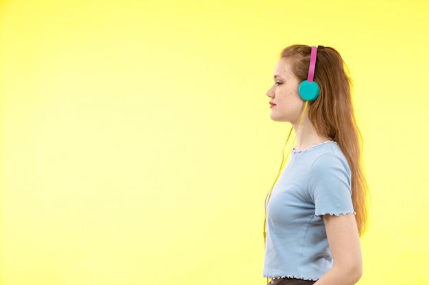 Вид спереди молодая современная женщина в синей рубашке черных брюк в разноцветных наушниках слушает музыку