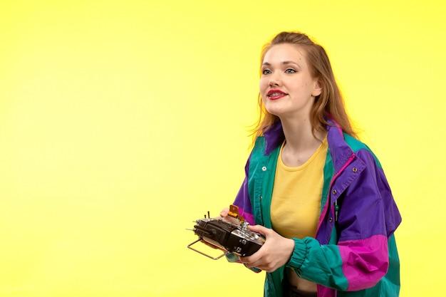 Вид спереди молодая современная женщина в желтой рубашке черных брюк и красочной куртке держит пульт дистанционного управления