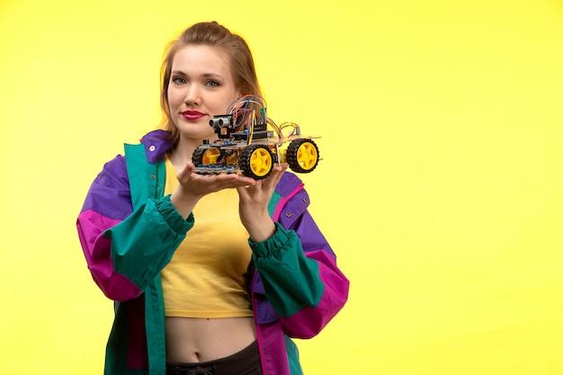 黄色のシャツの黒いズボンと幸せな表情をポーズのおもちゃの車を保持しているカラフルなジャケットの正面の若い現代女性