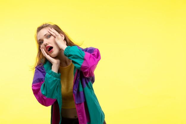 黄色いシャツの黒のズボンとカラフルなジャケットポーズで驚いた恐ろしい表情で正面の若い現代女性