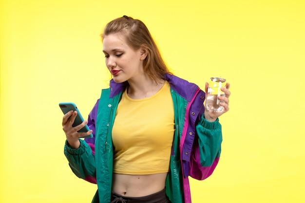黄色のシャツの黒いズボンと彼女の電話を使用してカラフルなジャケットの正面の若い現代女性