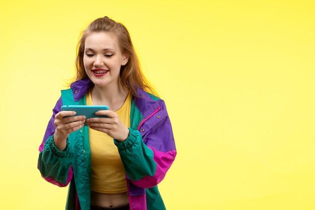 黄色のシャツの黒のズボンとカラフルなジャケットの電話の幸せな式で何かを見ている正面の若い現代女性