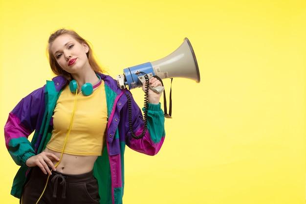 黄色のシャツの黒いズボンとメガホンのポーズを保持している色のイヤホンとカラフルなジャケットの正面の若い現代女性