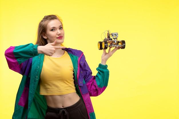 Вид спереди молодой современной женщины в желтой рубашке, черных брюках и красочной куртке с игрушечной машинкой в руках