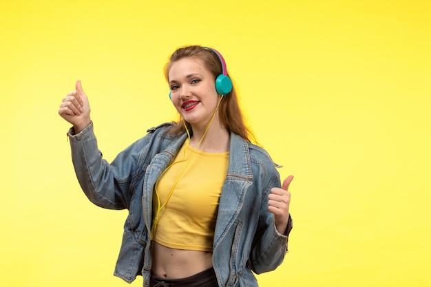 黄色のシャツの黒のズボンと音楽のポーズを聞いて色付きのイヤホンとジーンズのコートで正面の若い現代女性