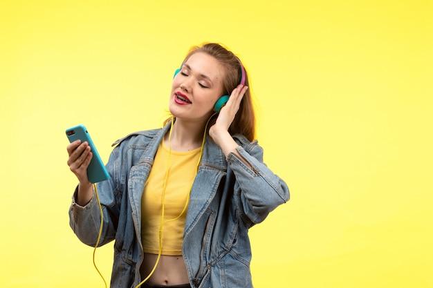 Вид спереди молодой современной женщины в желтой рубашке, черных брюках и джинсовой куртке с разноцветными наушниками, слушающих музыку, позирующей