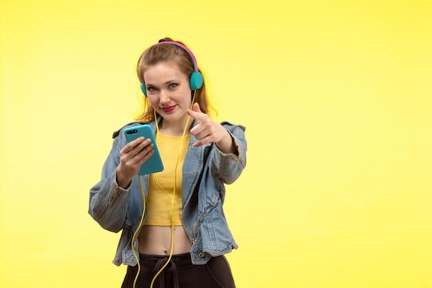 Вид спереди молодая современная женщина в желтой рубашке черные брюки и джинсовые пальто с цветными наушниками, используя телефон позирует