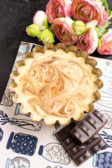 トップビューおいしいコーヒーケーキスイートチョコレートおいしい砂糖ベーカリーケーキと暗い机の上のバラ