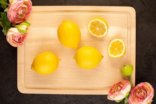 Вид сверху свежие лимоны кислые спелые целые и нарезанный мягкий цитрусовый тропический витамин желтый на темном столе