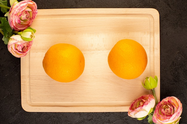 トップビューフレッシュオレンジサワー熟した全体とスライスしたまろやかな柑橘系トロピカルビタミンイエロー暗い机の上