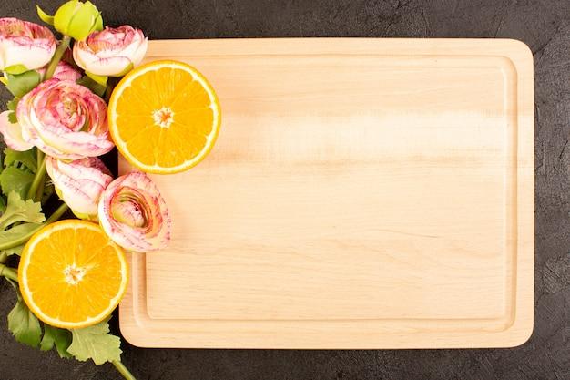 Вид сверху свежие апельсины кислые спелые целые с сушеными розами, мягкий цитрусовый тропический витамин желтый на темном столе