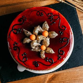 Фруктовый торт сверху с кремовым сиропом красного цвета, украшенный внутри белой тарелкой
