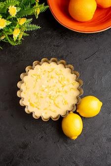 トップビューレモンケーキは暗い机の上に甘いエキゾチックなベーカリーケーキを酸っぱい