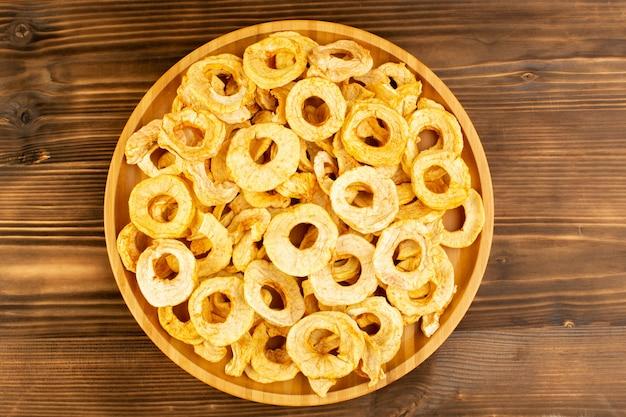 Вид сверху ананасовых сушеных колец внутри тарелки сухофруктов кислый вкусный неповторимый вкус на коричневом деревянном столе фрукты экзотические сухие