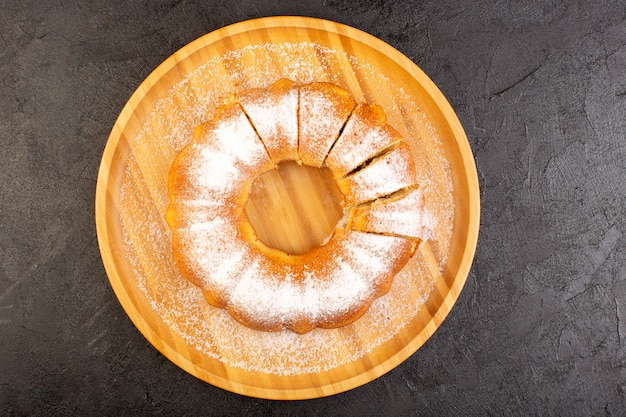 Вид сверху нарезанный порошкообразный торт сладкий вкусный запеченный круглый на деревянном столе сладкое печенье кондитерское