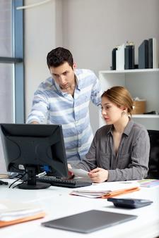 昼間の建物の仕事の活動中にオフィスの中で若い男と話したり何かを話し合ったりする灰色のシャツでフロントの距離ビューの若い美しい女性