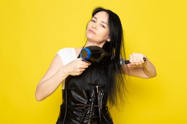 Вид спереди красивая женская парикмахерская в белой футболке черная накидка с кисточками с вымытыми волосами сушка расчесывает волосы позирует на желтом фоне стилист парикмахерская прическа