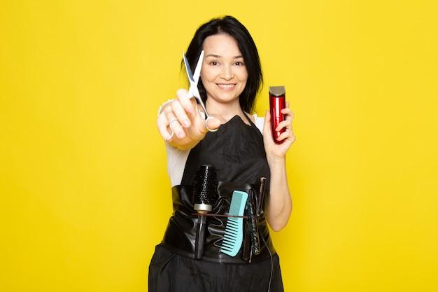 Вид спереди красивая женская парикмахерская в белой футболке черная накидка с кисточками с вымытыми волосами держит ножницы и машинку улыбаются на желтом фоне парикмахера-стилиста за волосами