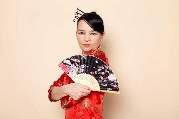 Вид спереди красивая японская гейша в традиционном красном японском платье с заколками для волос, держащая складной веер элегантно на кремовом фоне церемонии японии