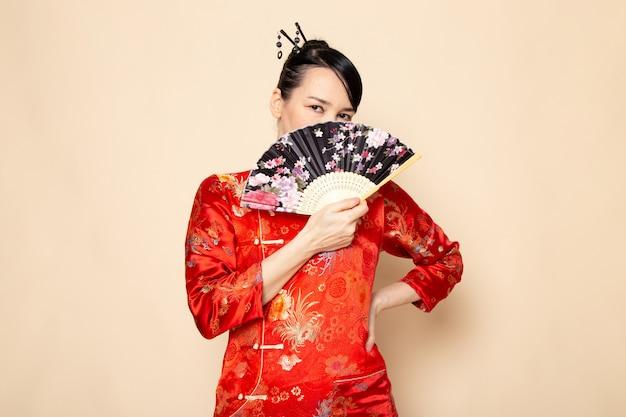 伝統的な赤い和服で美しい日本の芸者のヘアスティッククリーム色の背景の日本でエレガントな扇子を保持しているポーズで正面