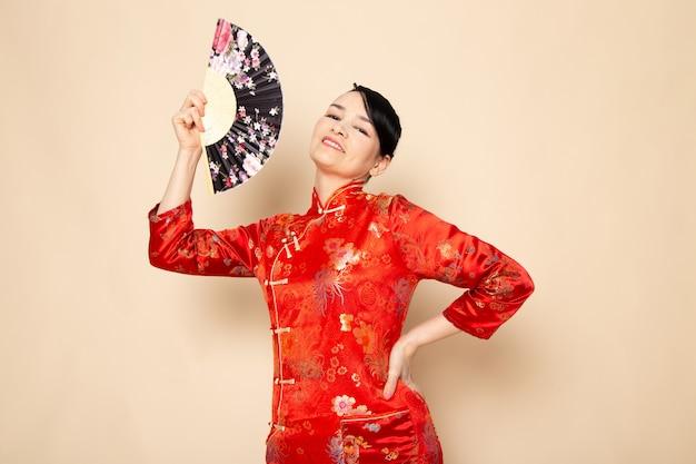 Вид спереди красивая японская гейша в традиционном красном японском платье с заколками для волос, держащей складной веер, улыбаясь на кремовом фоне церемонии японии