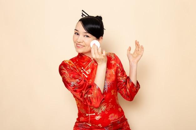 Вид спереди прекрасной японской гейши в традиционном красном японском платье с заколками для волос, держащей маленький белый хлопок, очищающей ее лицо на кремовом фоне церемонии японии