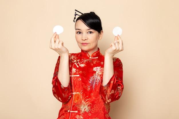 クリーム色の背景にエレガントな小さな白い綿を保持しているポーズをとって髪棒でポーズをとって伝統的な赤い和服で正面の美しい日本の芸者